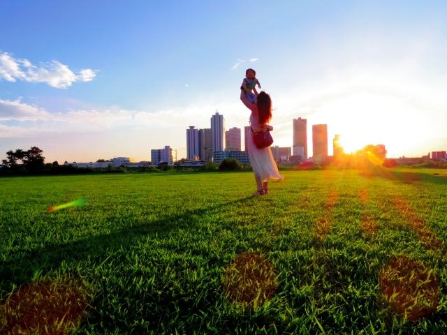 草むらの中で高い高いをする母と子